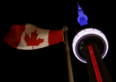 The landmark CN Tower is lit blue, white and red in the colors of the French flag following Paris attacks, in Toronto November 13, 2015. Canadian Prime Minister Justin Trudeau said on Friday it was too soon to say whether the deadly attacks in Paris would prompt him to reconsider his pledge to withdraw Canada from airstrikes against Islamic State militants in the Middle East. REUTERS/Chris Helgren - RTS6XJ7
