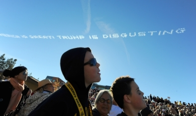 "Parade spectators watch as airplane sky writers write a message ""America is great! Trump is disgusting"" above the parade route during the 127th Rose Parade in Pasadena, Calif., Friday, Jan. 1, 2016. (AP Photo/Michael Owen Baker)"